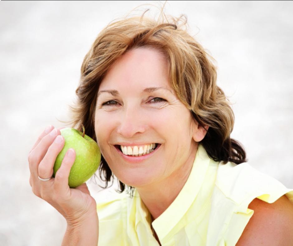 mujer madura saludable mostrando una preciosa manzana verde