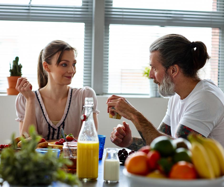 Pareja tomando en su casa un desayuno muy saludable sintiéndose muy a gusto