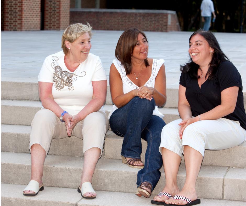 Mujeres charlando animadamente sentadas en las escaleras de cualquier calle, sintiéndose muy bien