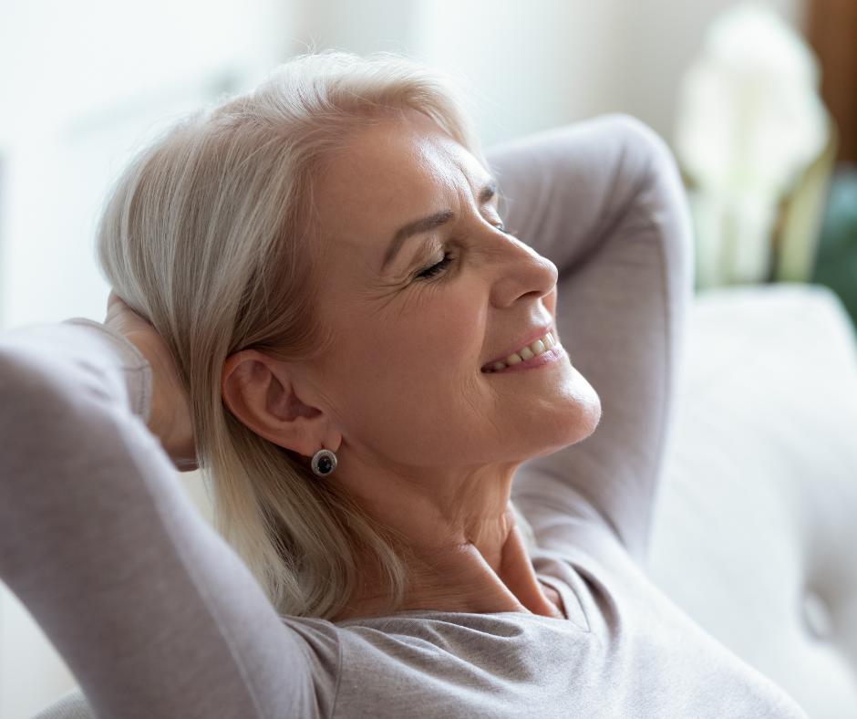 Mujer de más de 55 recostada en un sofá, apoyando su cabeza en sus manos recogidas por detrás y relajándose, con cara de satisfacción. Se siente muy bien.